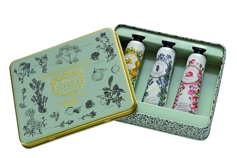 mint green and gold tin holding three miniature size tubes of hand lotion in various floral patterns