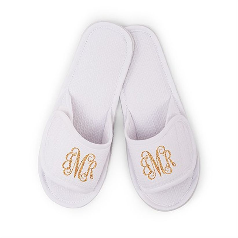 pair of white waffle knit slippers with gold glitter monogram on top