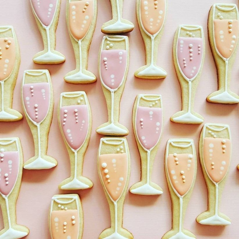 cookies shaped like champagne glasses decorated with pale pink and orange icing