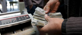 A man counts wads of U.S. dollars on a money counting machine at a currency exchange shop in Baghdad December 21, 2015. REUTERS/Khalid al Mousily