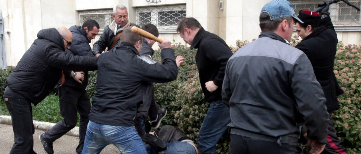 "Pro-Russian ""self-defence"" activists use a bat and a whip to beat a pro-Ukrainian supporter during clashes in Sevastopol on March 9, 2014. Pro-Kiev and pro-Moscow groups clashed in the Crimean city of Sevastopol on March 9 following a rally in support of Ukraine"