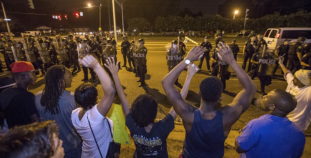 """Protesters in Baton Rouge, LA shout """"Hands up, don't shoot"""" as law enforcement stand watch (Getty Images)"""