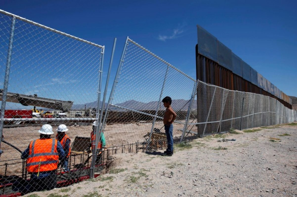 A boy looks at U.S. workers building a section of the U.S.-Mexico border wall at Sunland Park, U.S. opposite the Mexican border city of Ciudad Juarez, Mexico. REUTERS/Jose Luis Gonzalez