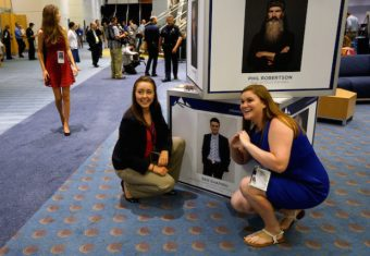 Women pose for a photo with photos of speakers, including Ben Shapiro (lower) and Phil Robertson, at the Western Conservative Summit in Denver July 1, 2016. REUTERS/Rick Wilking