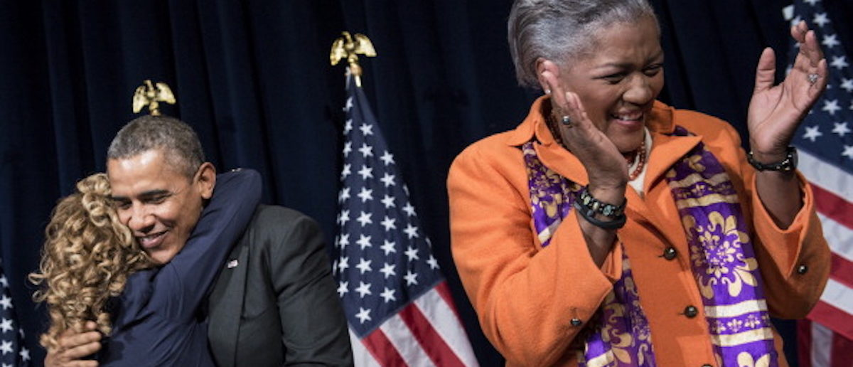 Donna Brazile (R) claps while US President Barack Obama (C) hugs Rep Debbie Wasserman Schultz (D-FL)before speaking to the Democratic National Committee at the Capital Hilton February 28, 2014 in Washington, DC. Obama spoke about the 2014 midterm elections. AFP (Photo: BRENDAN SMIALOWSKI/AFP/Getty Images)