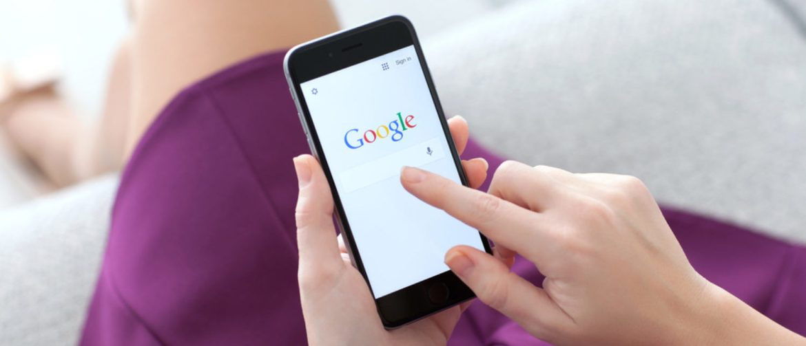 Woman holding a smartphone while searching through Google. [Shutterstock - Denys Prykhodov]