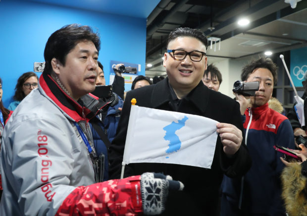 Ice Hockey � Pyeongchang 2018 Winter Olympics � Women Preliminary Round Match - Korea v Japan - Kwandong Hockey Centre, Gangneung, South Korea � February 14, 2018 - Kim Jong-un impersonator holds a Korean unification flag. REUTERS/Lucy Nicholson