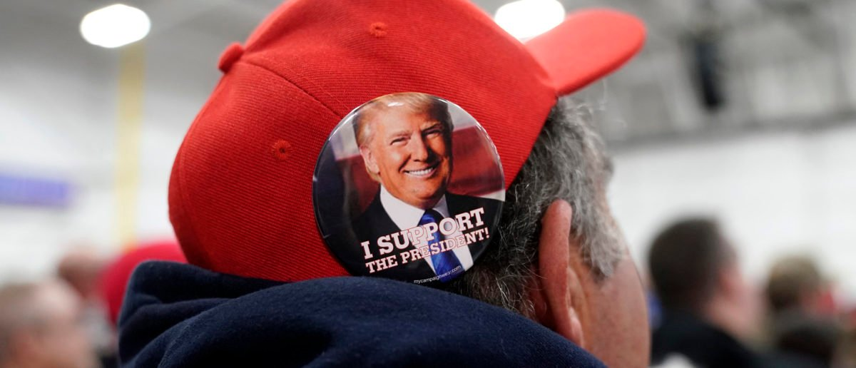 A supporter wears a hat with a Trump button as U.S. President Donald Trump speaks in support of Republican congressional candidate Rick Sacconne during a Make America Great Again rally in Moon Township, Pennsylvania, U.S., March 10, 2018. REUTERS/Joshua Roberts