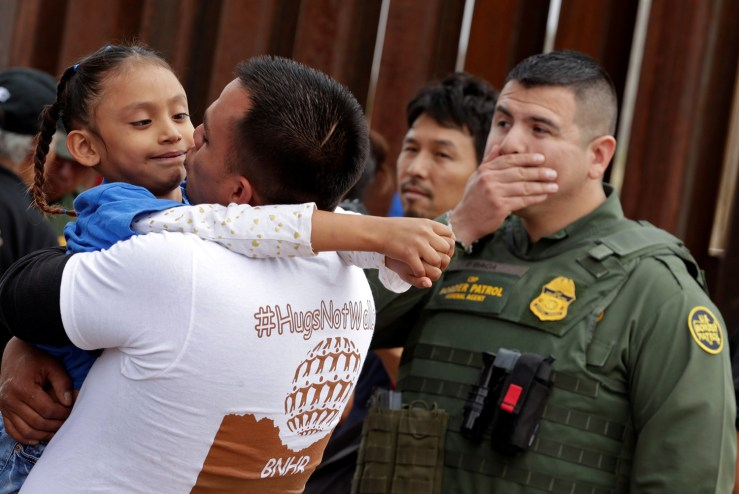 A man embraces a child as an U.S. border patrol federal agent reacts during a brief reunification meeting of relatives separated by deportation and immigration called