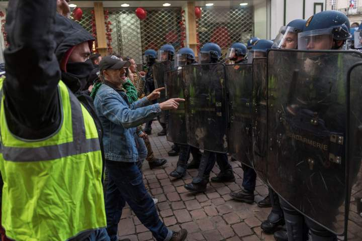 Protestors wearing yellow vests (gilets jaunes), face French riot police officers during a demonstration against rising costs of living they blame on high taxes, in Le Puy-en-Velay, on December 8, 2018, - The