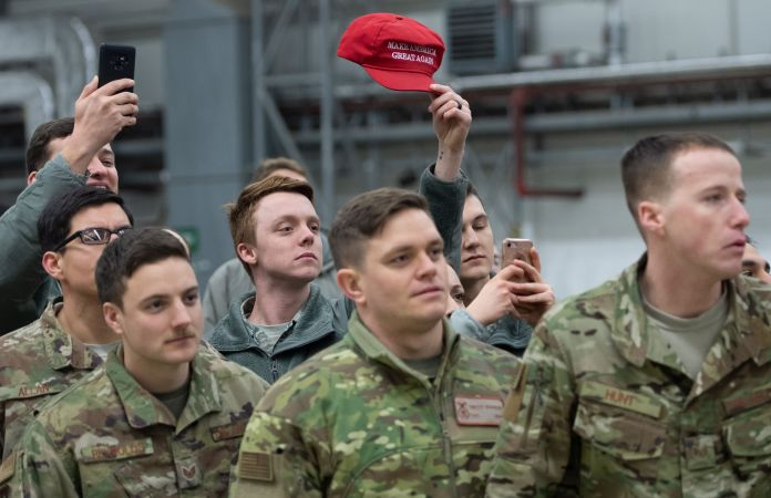 "A member of the US military holds up a ""Make America Great Again"" hat as US President Donald Trump and First Lady Melania Trump greet members of the US military during a stop at Ramstein Air Base in Germany, on December 27, 2018. - President Donald Trump used a lightning visit to Iraq -- his first with US troops in a conflict zone since being elected -- to defend the withdrawal from Syria and to declare an end to America's role as the global ""policeman."" (Photo by SAUL LOEB/AFP/Getty Images)"