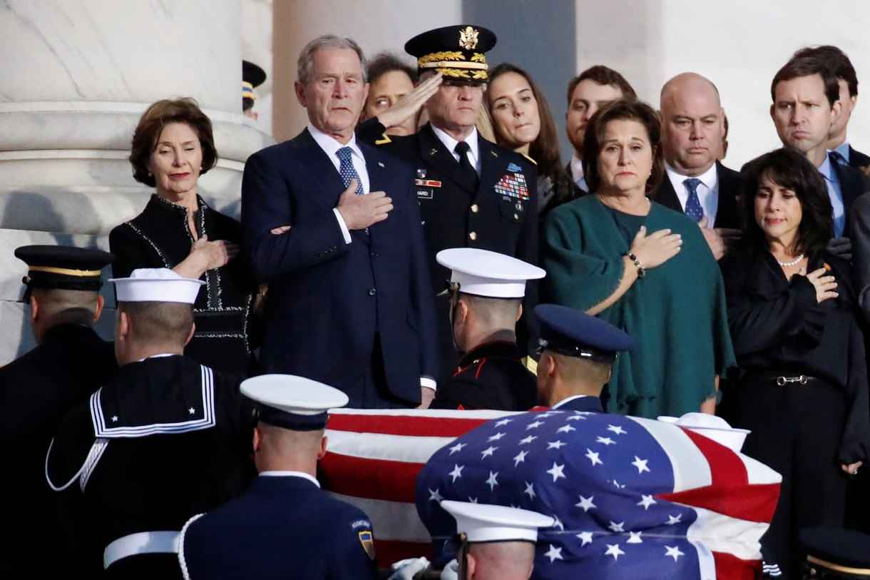 Former President George W. Bush and other family members watch as the flag-draped of former President George H.W. Bush is carried by a joint services military honor guard to lie in state in the rotunda of the U.S. Capitol, Monday, Dec. 3, 2018, in Washington. (Alex Brandon/Pool via Reuters)