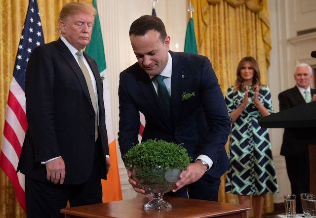 Irish Prime Minister Leo Varadkar presents a bowl of shamrocks to US President Donald Trump alongside US First Lady Melania Trump (R) during a Shamrock Bowl Presentation in honor of St. Patrick's Day in the East Room of the White House in Washington, DC, March 14, 2019. (Photo credit: SAUL LOEB/AFP/Getty Images)