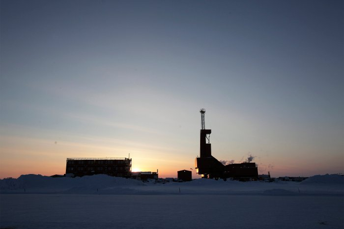 The sun sets behind an oil drilling rig in Prudhoe Bay, Alaska