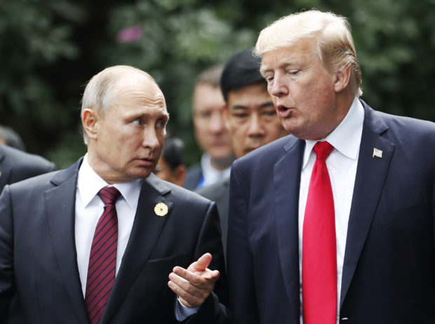 US President Donald Trump (R) and Russia's President Vladimir Putin talk as they make their way to take the