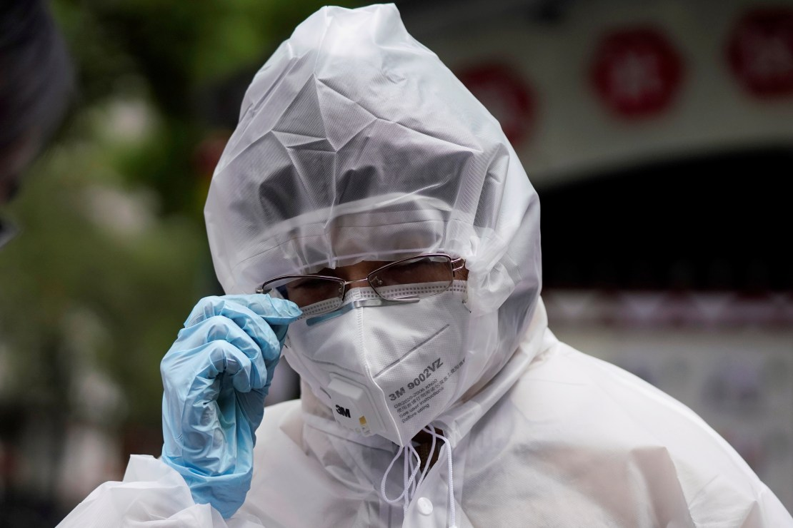 A woman wearing protective gear adjusts her glasses in Wuhan, Hubei province, the epicentre of China's coronavirus disease (COVID-19) outbreak, March 30, 2020. REUTERS/Aly Song