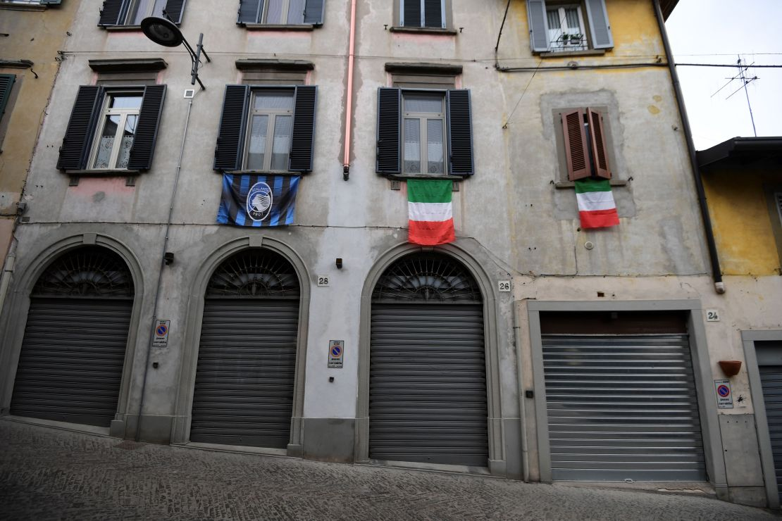 A general view shows Italian flags and an Atalanta Bergamo football team flag (L) hanging over closed shops in a deserted street of Albino near Bergamo, Lombardy, on March 25, 2020, during the country's lockdown following the COVID-19 new coronavirus pandemic. (Photo by MIGUEL MEDINA/AFP via Getty Images)