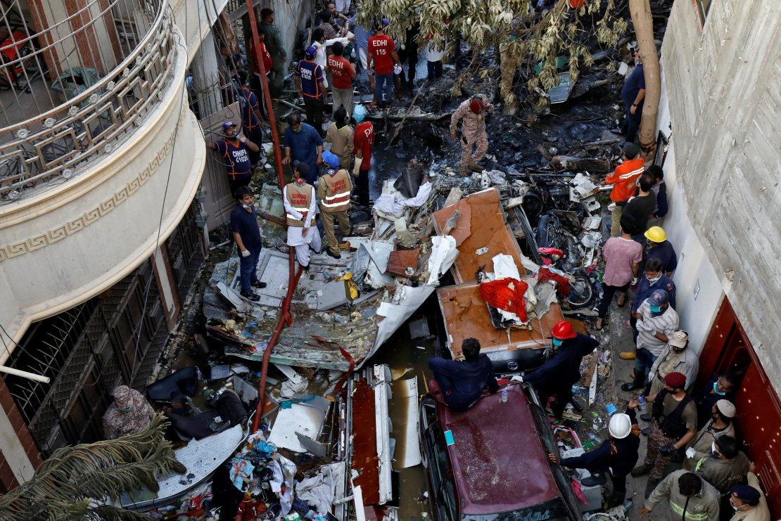 Rescue workers gather at the site of a passenger plane crash in a residential area near an airport in Karachi, Pakistan May 22, 2020. REUTERS/Akhtar Soomro - RC2PTG9FEVAS