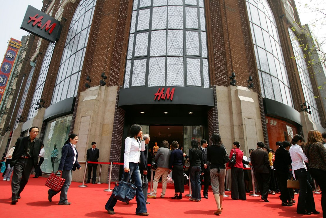 Chinese shoppers wait in line to enter the newly opened H&M store, the first in mainland China, on April 13, 2007 in Shanghai, China. Australian pop singer Kylie Minogue attended the launch. (Photo by Cancan Chu/Getty Images)