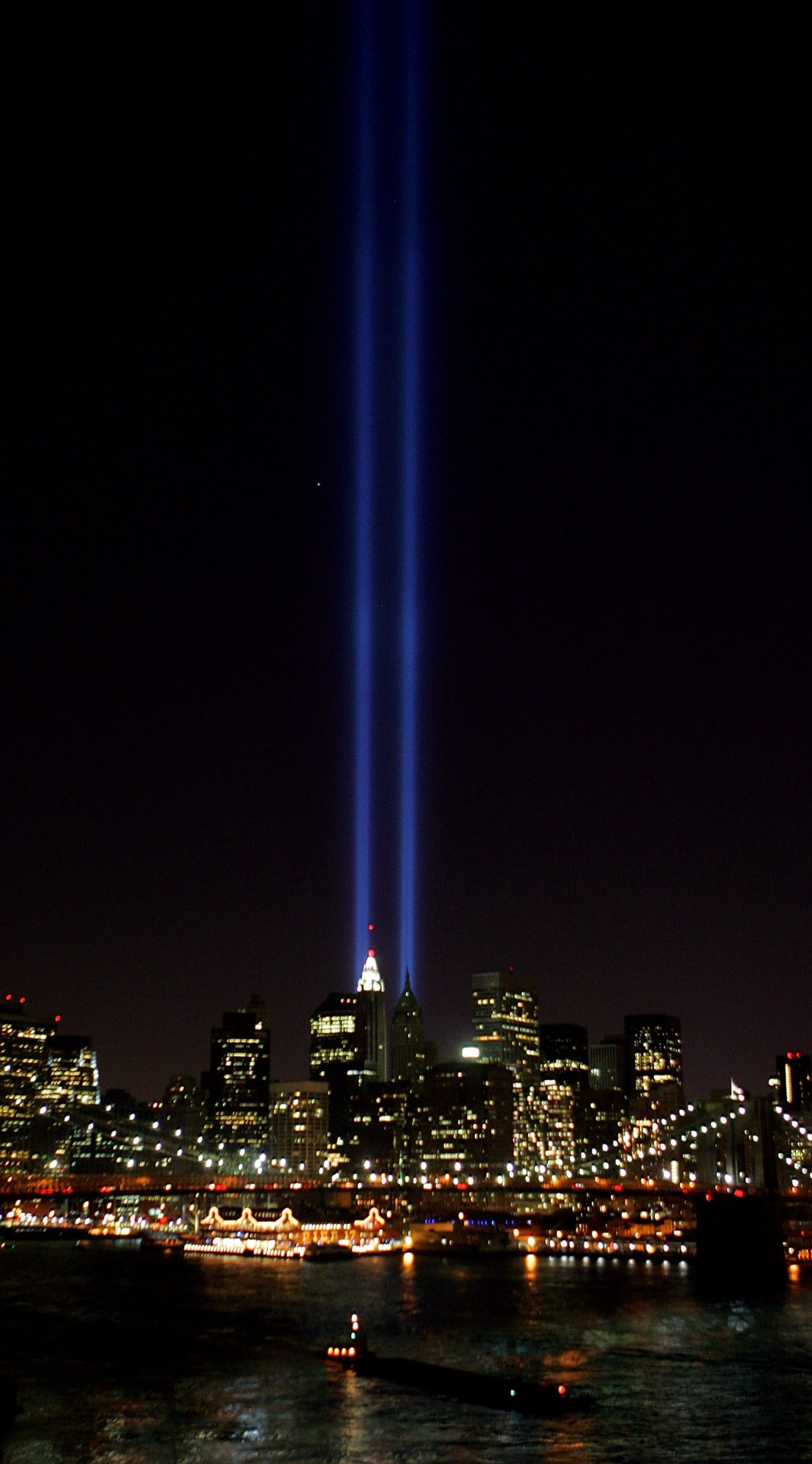 NEW YORK - SEPTEMBER 11: Beams of light shine into the sky behind the Brooklyn Bridge and above the Manhattan skyline on September 11, 2005 in New York City. The lights pay tribute to those who lost their lives when the World Trade Center was attacked four years ago. (Photo by Daniel Berehulak/Getty Images)