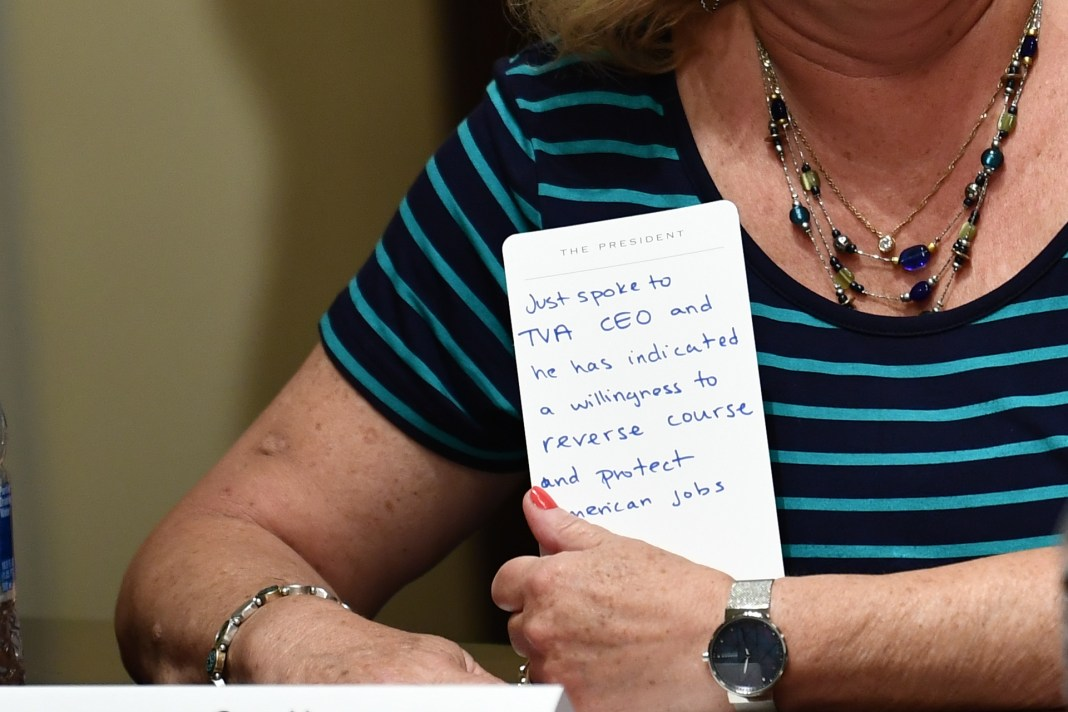 Gay Henson, President of Engineering Association, Tennessee Valley Authority holds a note card as US President Donald Trump speaks, before signing an Executive Order on Hiring American at the White House on Aug. 3. (Brendan Smialowski/AFP via Getty Images)