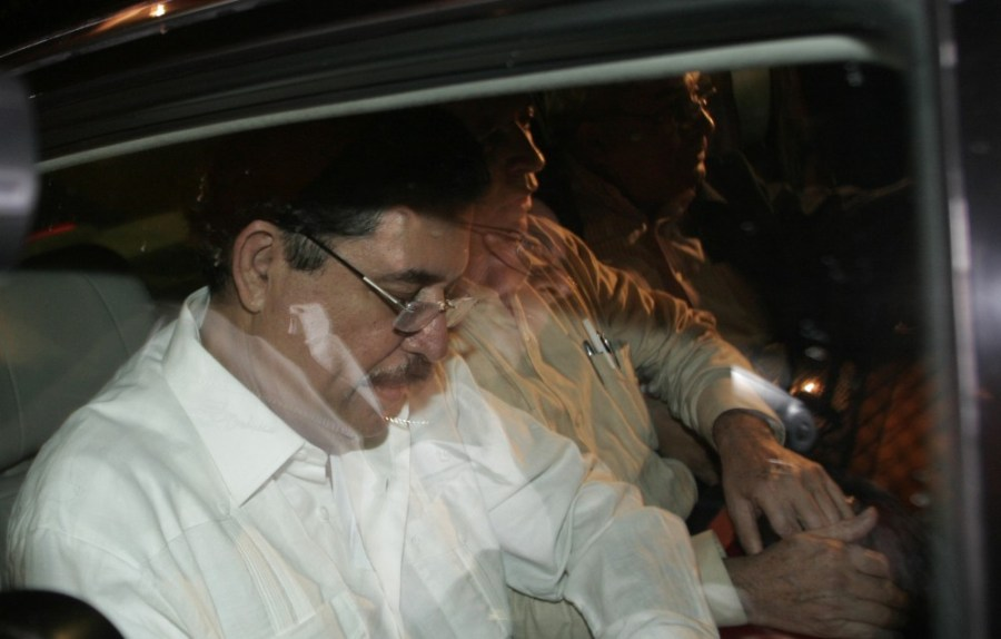 Ousted Honduras' President Manuel Zelaya, left, looks down inside a car on his way to the airport where he will board a flight to Nicaragua on the outskirts of San Jose, Sunday, June 28, 2009. Soldiers seized Honduras' national palace and sent the President Zelaya into exile in Costa Rica on Sunday, hours before a disputed constitutional referendum. Zelaya, an ally of Venezuelan President Hugo Chavez, said he was victim of a coup. Honduras' Congress sworn in Sunday congressional leader Roberto Micheletti as the country's new President. (AP Photo/Kent Gilbert)
