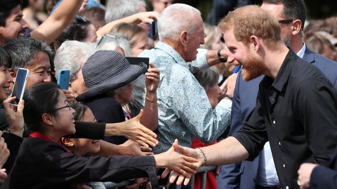 Pangeran Harry tertawa saat menyalami anak kecil di Taman Pemerintah Rotorua, Selandia Baru, Rabu (31/10). Pangeran Harry dan Meghan Markle sedang dalam tur tiga minggu di Australia, Selandia Baru, Tonga, dan Fiji. (Michael Bradley/Pool/AFP)