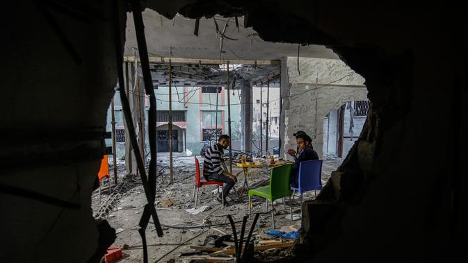 Orang-orang Palestina yang diamputasi berbuka puasa di sebuah pusat komunitas yang dihancurkan selama eskalasi dua hari, di Rafah, Jalur Gaza selatan (8/5/2019). Perang antara Palestina dan Israel telah menewaskan belasan orang. (AFP Photo/Said Khatib)