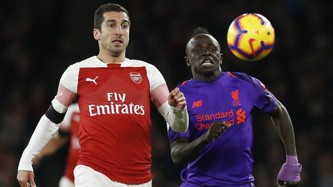 Gelandang Arsenal, Henrikh Mkhitaryan, beradu cepat dengan gelandang Liverpool, Sadio Mane, pada laga Premier League di Stadion Emirates, London, Minggu (3/11). Kedua klub bermain imbang 1-1. (AFP/Ian Kington)