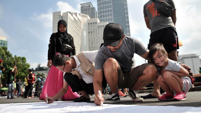 Warga membubuhkan tanda tangan pada kain saat peringatan Hari Bumi di CFD Bundaran HI, Jakarta, Minggu (21/4). Aksi ini sekaligus mengajak masyarakat untuk lebih peduli terhadap lingkungan. (merdeka.com/Iqbal Nugroho)
