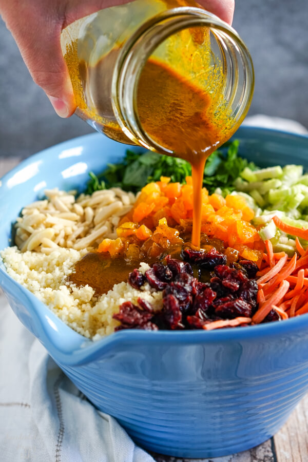 The curry dressing is poured over the top of the curried couscous salad.
