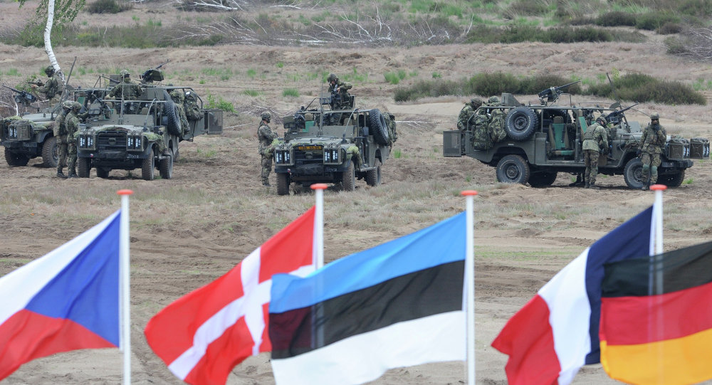 Flags wave in front of soldiers who take positions with their army vehicles during the NATO Noble Jump exercise on a training range near Swietoszow Zagan, Poland, Thursday, June 18, 2015