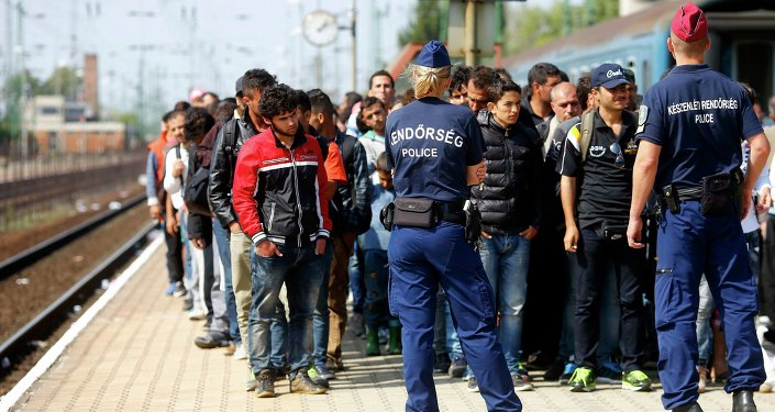 Hungarian police officers stand guard as migrants disembark from a train at the railway station in the town of Hegyeshalom next to the Austrian Hungarian border, Hungary September 13, 2015