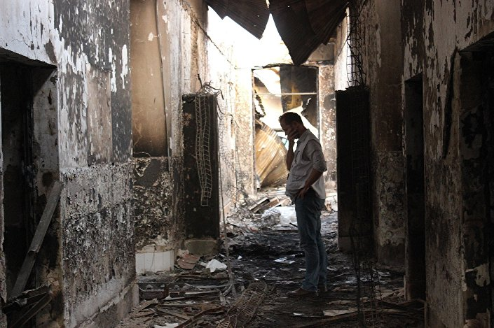 In this Friday, October 16, 2015 photo, an employee of Doctors Without Borders walks inside the charred remains of their hospital after it was hit by a US airstrike in Kunduz, Afghanistan.