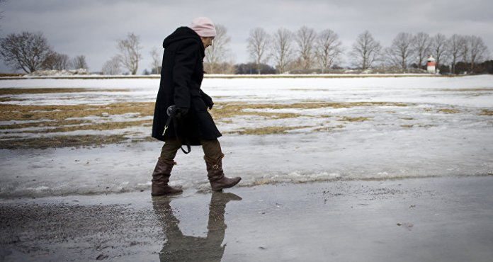 An elderly woman walks on melted snow in Djurgaarden area in Stockholm on March 21, 2011