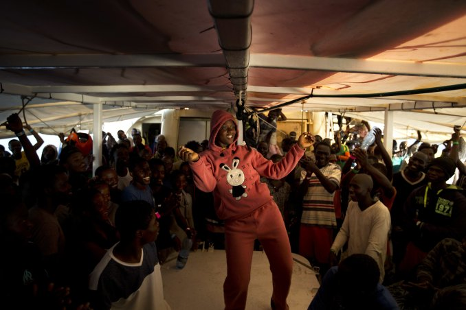 A woman from Nigeria dances on the deck of the Golfo Azzurro rescue vessel as it arrives at the port of Pozzallo, south of Sicily, Italy, with hundreds of migrants aboard, rescued by members of Proactive Open Arms NGO, on Saturday, June.17, 2017