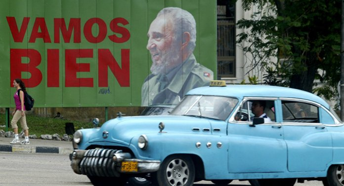 A taxi passes a sign with Cuban President Fidel Castro