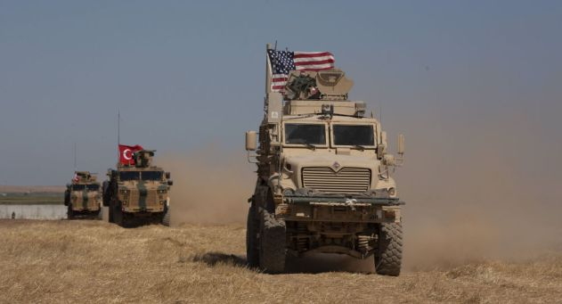 In this Sept. 8, 2019, photo, Turkish and American armored vehicles conduct the first joint patrol in the so-called safe zone on the Syrian side of the border with Turkey near Tal Abyad, Syria