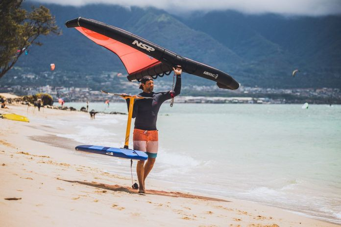 Pro wind foiler walking with kite and board on the beach
