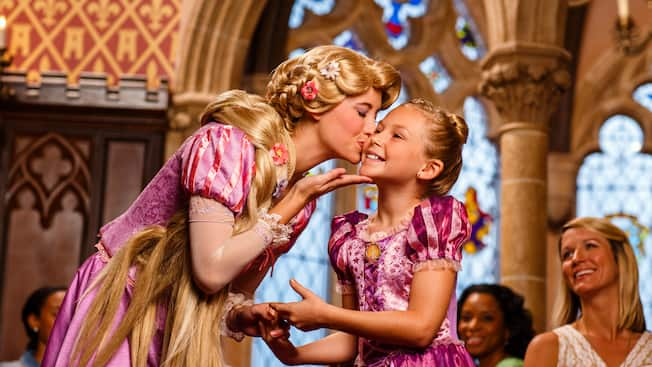 Princess Rapunzel kisses a girl on the cheek at Cinderella's Royal Table