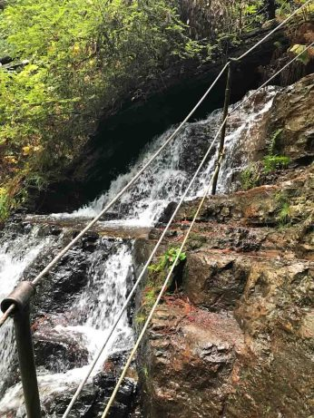 The steps climb right beside the cascade