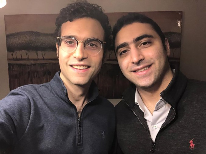 Two people smile at the camera