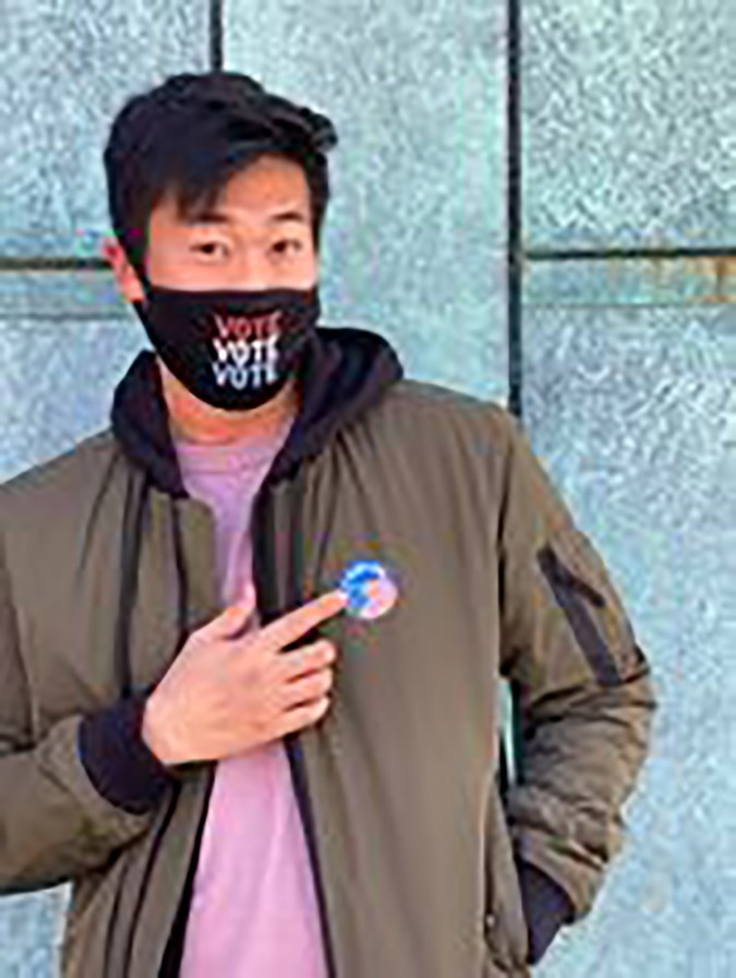 """Student wearing a """"vote"""" mask and pointing to a """"vote"""" sticker"""