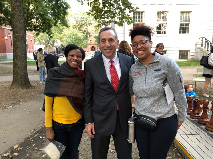 Two students pose for a photo with Larry Bacow before the pandemic