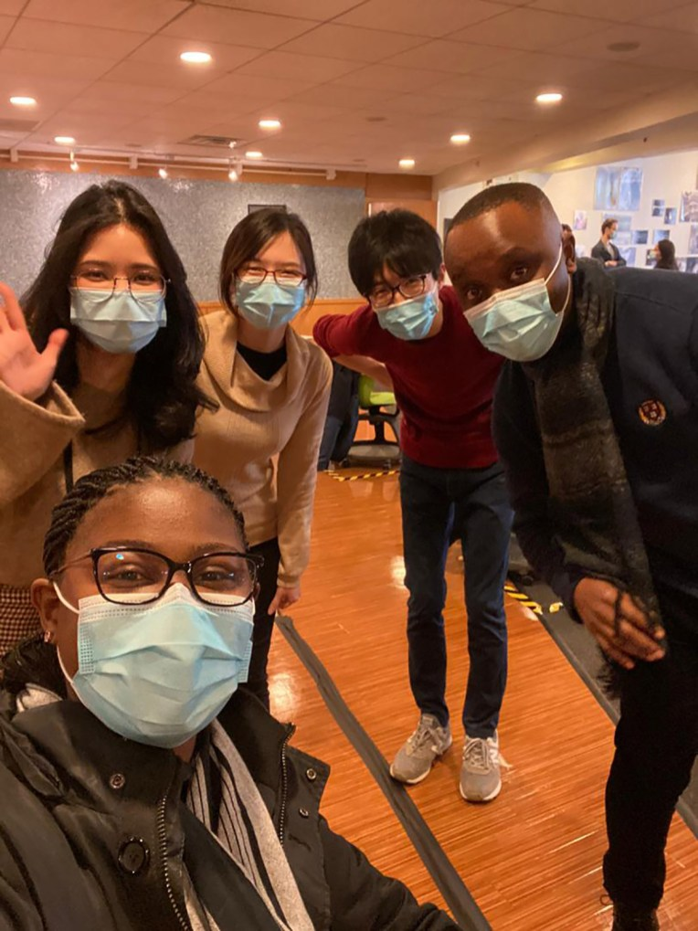 Hybrid learning students pose with masks on in Kresge cafeteria