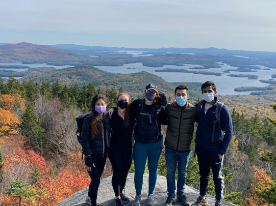 Five students stand on top of a rock, on top of a mountain, wearing masks