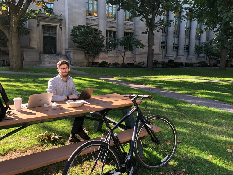 A student sits with laptop at a picnic table during the summer in Harvard Yard