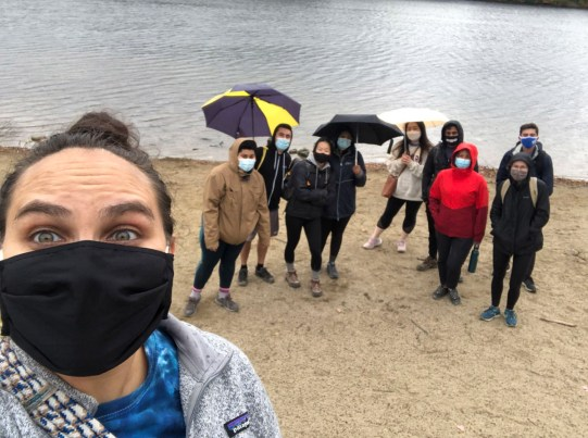Students pose in front of lake wearing masks