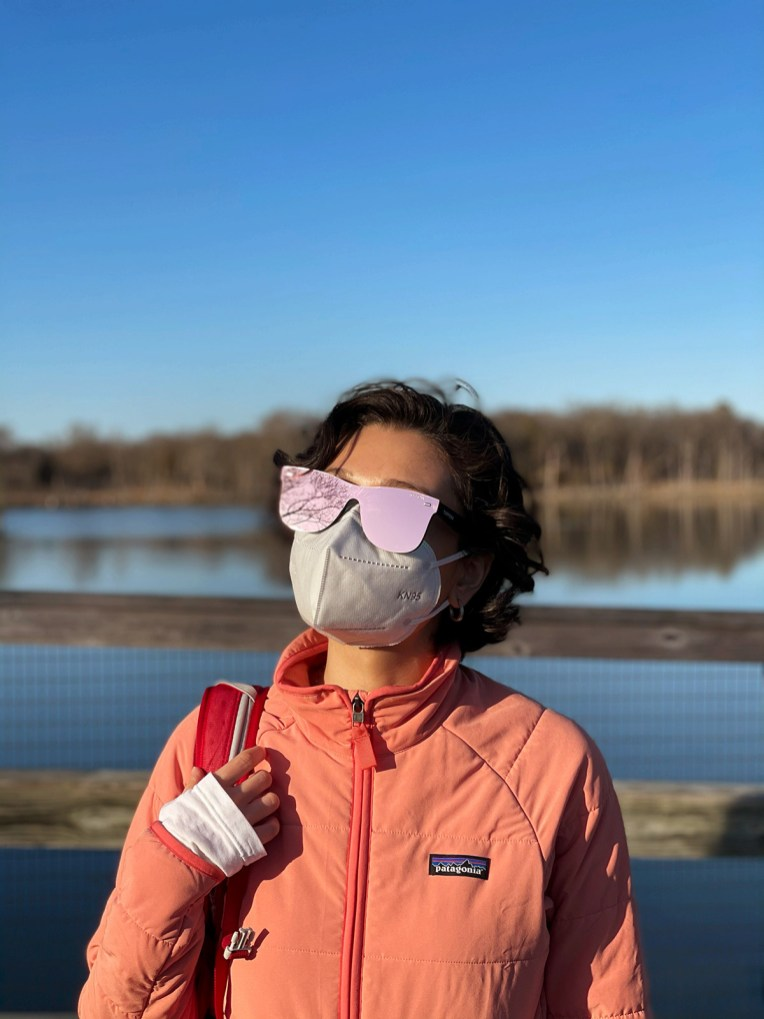 Student photographed artistically by lake wearing mask and very reflective sunglasses