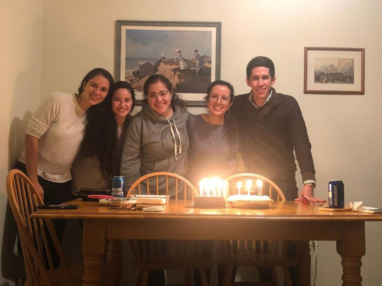 Five people pose in front of birthday cake and lit candles